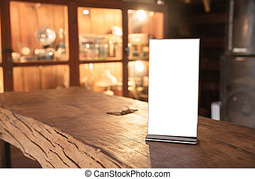 Mock up Menu frame in Bar restaurant, Stand for booklets with white sheets of paper acrylic tent card on wooden table on cafeteria blurred background.