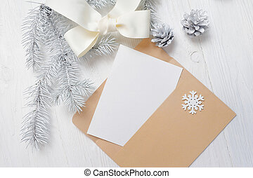 Mockup Christmas greeting card letter in envelope with white tree and cone, flatlay on a wooden background, with place for your text