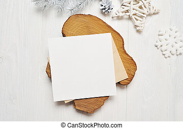 Mockup Christmas greeting card letter in envelope with white tree, flatlay on a white wooden background, with place for your text