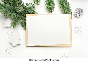 Mockup Christmas greeting card with envelope on wooden white background with fir tree branches and happy new year decorations. Top view copyspace