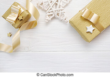 Mockup Christmas star and gold gift ribbon, flatlay on a white wooden background, with place for your text