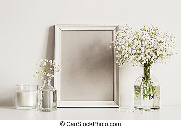mockup composition with photo frame, white flowers and candle. Copy space for artwork