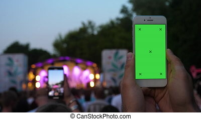 Hand of young man holding phone recording video in front of blurred concert background.