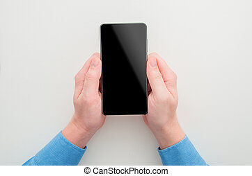 Mockup image of a man with blue shirt holding black mobile phone with blank screen on white background