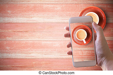 Mockup image of hand holding white mobile phone with cup of coffee