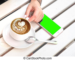 Mockup image of white mobile phone with blank black screen and hand holding hot latte coffee on vintage wood table in cafe