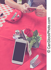 Mockup image of white mobile phone with blank white screen on red background in restaurant. Tropical Bali island, Indonesia. Woman hands with smartphone on blurred background.