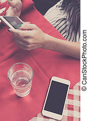 Mockup image of white mobile phone with blank white screen on red background in restaurant. Tropical Bali island, Indonesia. Woman hands with smartphone on a background.