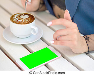 Mockup image of white mobile phone with green screen and hand holding phone. coffee on the table