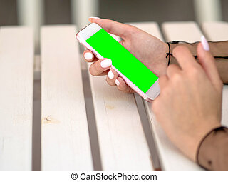 Mockup image of white mobile phone with green screen and hand holding phone.