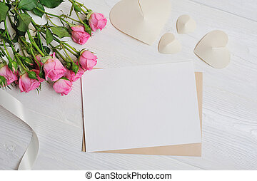 Mockup letter white origami hearts made of paper with pink roses, card for Valentine's Day. Flat lay, top view with a place for your text