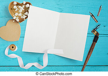 mockup Letter with paper hearts, kraft box with flowers for greeting card St. Valentine's Day in rustic style with place for your text on a turquoise wooden background. Flat lay, top view mock up