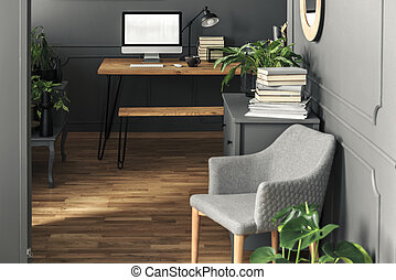 Mockup of computer desktop on wooden desk in workspace interior with grey armchair. Real photo