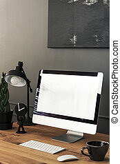 Mockup of computer desktop on wooden desk with lamp in dark home office interior. Real photo