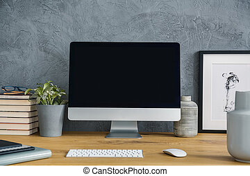Mockup of computer desktop on wooden desk with plant in grey workspace interior. Real photo