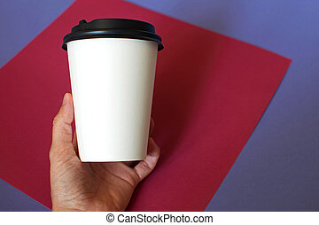 Mockup of female hand holding a coffee paper cup.