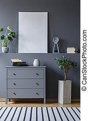Mockup of poster in grey living room interior with plant next to cabinet. Real photo