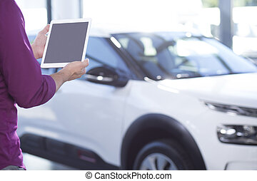 Mockup of tablet of car seller in dealing salon with...