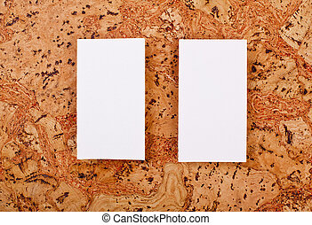 Mockup of white business cards at a cork background