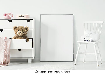 Mockup of white empty poster between chair and cabinet in child's room interior. Real photo