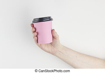 Mockup of woman hand holding a pink coffee paper cup on white wall background.
