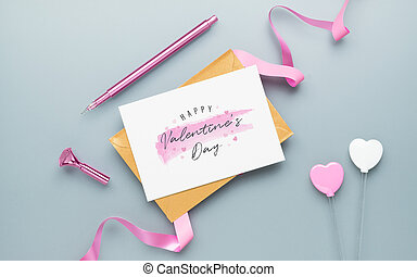 Mockup postcard and envelope on grey background with Happy valentines day, handy craft, gift box bow and pen. Mock up for elegant design. Flat lay top view valentine's day background.