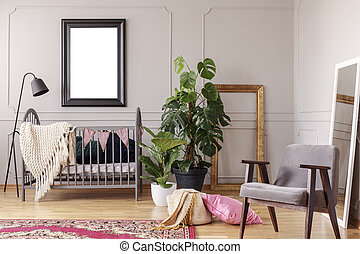 Mockup poster in black frame above grey wooden crib in stylish baby room interior with green plants in pots and retro armchair, real photo