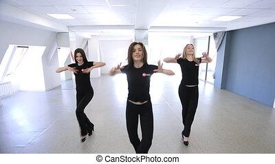 modèles, trois, jeune, début, en mouvement, danse, classe, synchronously