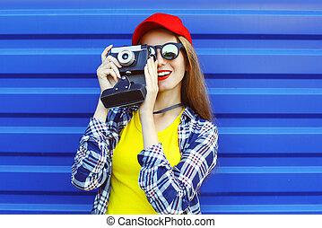 moda, carino, fresco, ragazza, il portare, uno, colorito, vestiti, con, retro, macchina fotografica, riprese, sopra, sfondo blu