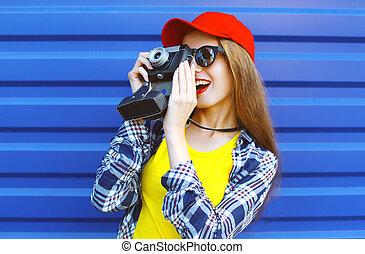 moda, carino, fresco, ragazza, il portare, uno, colorito, vestiti, con, vecchio, retro, macchina fotografica, riprese, sopra, sfondo blu