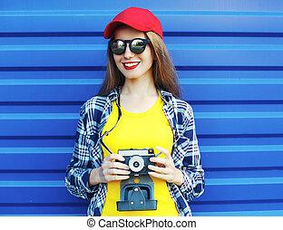 moda, carino, ragazza sorridente, il portare, uno, colorito, vestiti, con, retro, macchina fotografica, sopra, sfondo blu