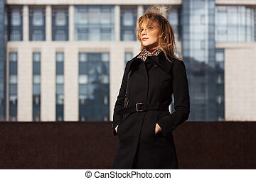 moda, loura, mulher, em, revestimento preto, andar, ligado, cidade, rua