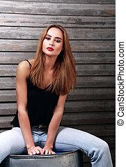 moda, maquilagem, mulher, com, cabelo longo, estilo, em, calças brim azuis, e, lábios vermelhos, sentando, ligado, ferro, barril, ligado, parede, backgroud