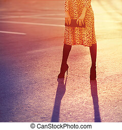 moda, mujer, en, vestido de leopardo, con, embrague, bolso, posar, tarde, en, ocaso, luz, vendimia, colores, foto