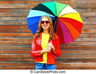 moda, mulher sorridente, com, coloridos, guarda-chuva, em, dia outono, sobre, madeira, fundo