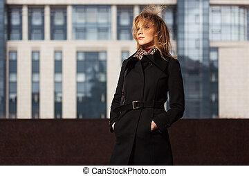 moda, rubio, mujer, en, abrigo negro, ambulante, en, la ciudad, calle