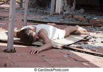 model acting a unconscious woman on the street after house explosion
