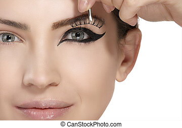 Model applying artificial eyelashes extension on smoky eye