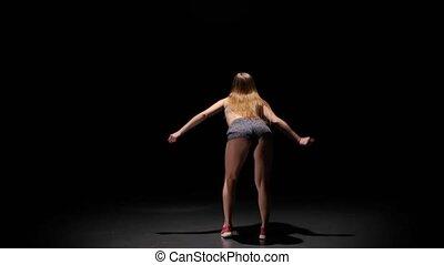 Model brunette woman dancing twerk her sexy buttocks. Dark studio