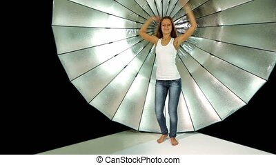 model dances in front of reflector in photo studio