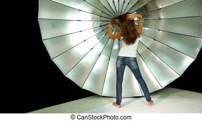 model dances in front of reflector in photo studio