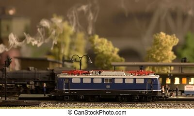 Model electric locomotive waiting for passengers at station.