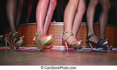 Model feets on high heels synchronously tap on floor. Runway show in nightclub.