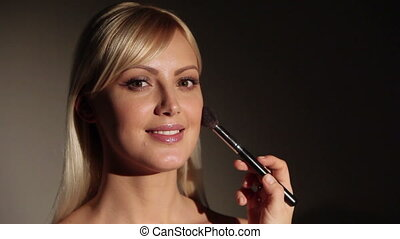 Model gets make up. Professional makeup artist applies blusher to model's face.