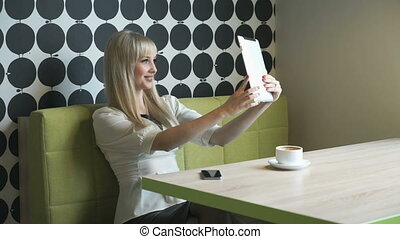 Model girl making selfie photo on computer tablet
