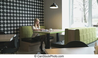 Model girl sitting in a cafe writes text in daily