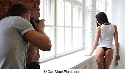 model, het poseren, in, een, t-shirt, en, black , slipjes , voor, een, fotograaf, dichtbij, de, venster