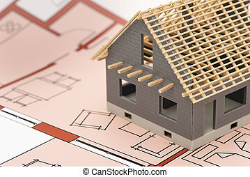 model home standing on construction plan