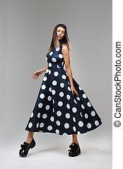 Model in a long polka dot dress dance