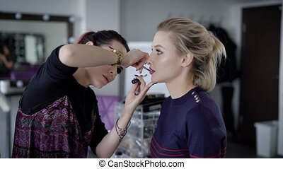 Model in beauty shop. The makeup artist applies with a brush dark lipstick for lips on an upper lip. The client sits quietly not to spoil work of the makeup artist and a make-up.